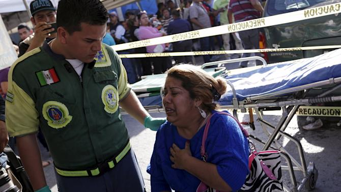 An inmate's family member is being looked after by a Green Cross worker outside the Topo Chico prison in Monterrey