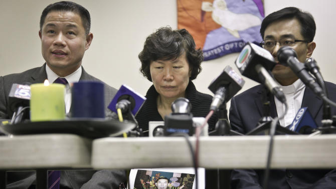Serim Han, center, holds a picture of her husband Ki-Suck Han, as she is flanked by New York City Comptroller John Liu, left,  and Rev. Won Tae Cho, Han's pastor, during a news conference on Wednesday, Dec. 5, 2012 in New York. A homeless man was arrested Wednesday in the death of Ki-Suck Han, who was pushed onto the tracks and photographed just before a train struck him.  (AP Photo/Bebeto Matthews)
