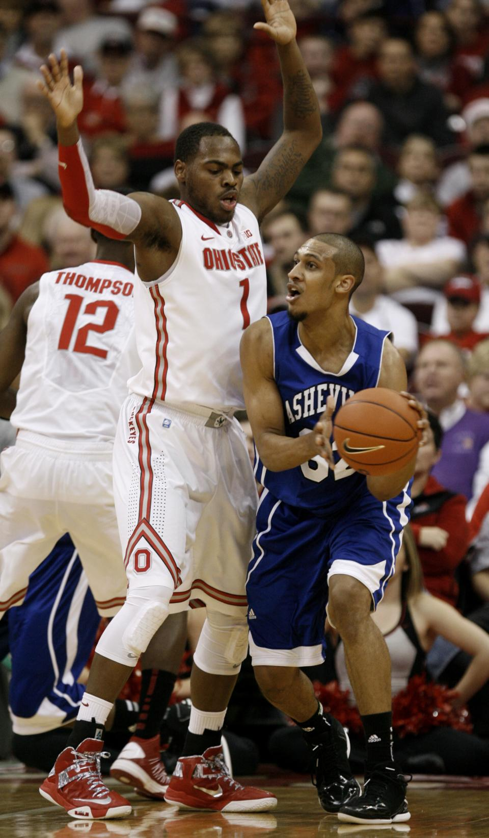 UNC-Asheville's Will Weeks, right, looks to pass around Ohio State's Deshaun Thomas during the first half of an NCAA college basketball game in Columbus, Ohio, Saturday, Dec. 15, 2012. (AP Photo/Paul Vernon)