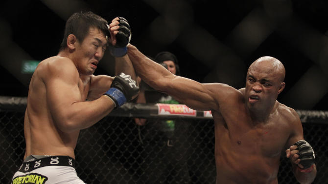 Defending middleweight champion Anderson Silva of Brazil, right, punches Japan's Yushin Okami in the middleweight title bout of the Ultimate Fighting Championship (UFC) 134 in Rio de Janeiro, Brazil, Saturday Aug. 27, 2011. Silva knocked out Okami in the second to defend his title. (AP Photo/Felipe Dana)
