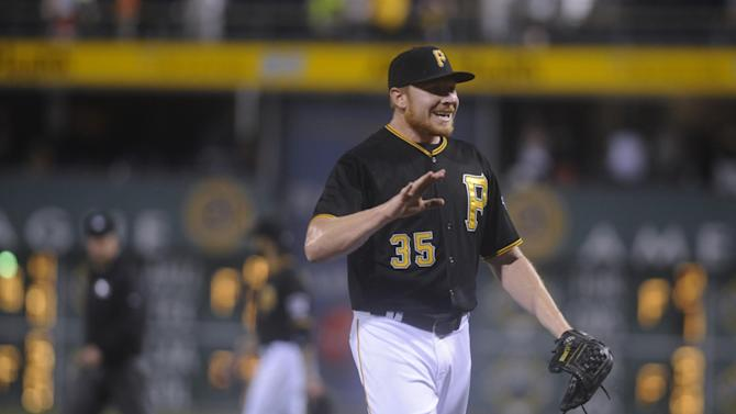 Pittsburgh Pirates Mark Melancon goes to high-five teammates after picking up the save in the Pirates' 3-2 victory over the San Diego Padres in a baseball game in Pittsburgh, Tuesday, July 7, 2015. (AP Photo/Vincent Pugliese)