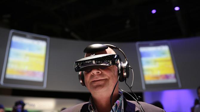 Juergen Boyny, of Germany, watches a video clip with a personal viewing device at the Sony booth at the International Consumer Electronics Show(CES) on Thursday, Jan. 9, 2014, in Las Vegas. (AP Photo/Jae C. Hong)