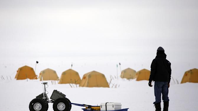 In this July 15, 2011 photo, atop roughly two miles of ice, with sleeping tents visible in the background, Dartmouth College engineering graduate Suk-Joon Lee helps test a prototype wheeled Arctic robot being developed for long-range instrument deployment, at Summit Station, a small U.S. National Science Foundation research center situated 10,500 feet above sea level, on top of the Greenland ice sheet. Across Greenland's vast white landscape, small teams of researchers from around the world are searching for clues to the potential effects of global warming on Greenland's ice. (AP Photo/Brennan Linsley)