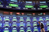 A reporter stands in front of screens showing the share price of newly debuted Facebook stock at the Nasdaq stock market moments after it went public, May 18. Facebook stumbled on its first trading day as shares ended barely above the starting price, raising questions about what will happen to the share price when the Nasdaq reopens on Monday
