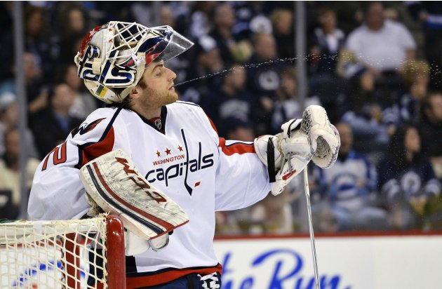 Capitals' goaltender Holtby spits out water during a break in the action against the Jets during their NHL hockey game in Winnipeg