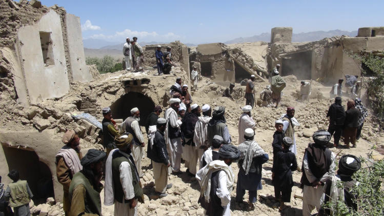 Afghan villagers gather at a house destroyed in an apparent NATO raid in Logar province, south of Kabul, Afghanistan on Wednesday, June, 6, 2012. Afghan officials and residents say a pre-dawn NATO airstrike aimed at militants in eastern Afghanistan killed civilians celebrating a wedding, including women and children. (AP Photo/Ihsanullah Majroh)