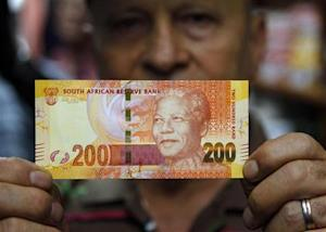 "A shop owner shows off South Africa's new banknotes, which features an image of former president Nelson Mandela on the front and images of the country's ""Big Five"" wild animals on the reverse, as they go into official circulation in Pretoria"