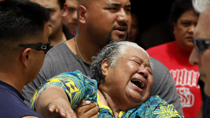 Luisa Seau, mother of Junior Seau, grieves in the driveway of the home were the former NFL star was found dead, Wednesday, May 2, 2012, in Oceanside, Calif. Junior Seau was found shot to death at his home in what police said appeared to be a suicide. He was 43. (AP Photo/Chris Carlson)