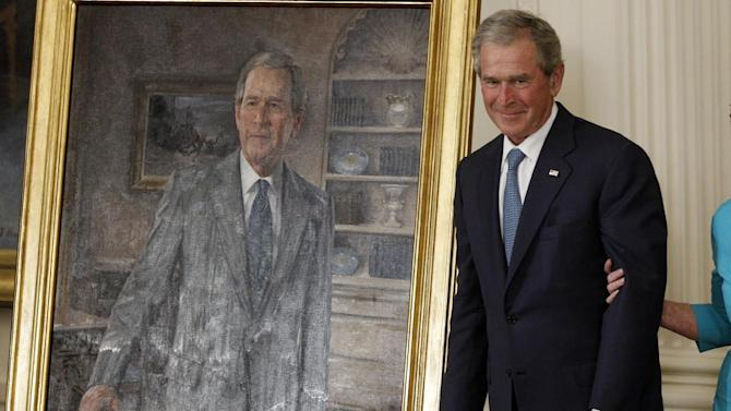Former President George W. Bush stands next to his official portrait, Thursday, May 31, 2012, in the East Room at the White House in Washington. (AP Photo/Charles Dharapak)