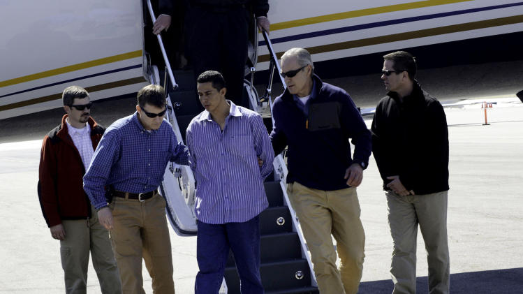 "In this photo provided by the FBI Denver Special Agents escort Rivera Gracias, one of the FBI's ""Ten Most Wanted Fugitives,"" off a plane, Wednesday, March 27, 2013 in Denver. Gracias was wanted in Jefferson County in the slaying of 69-year-old Richard Limon, whose beaten and stabbed body was found dumped along a roadside in 2011. (AP Photo/FBI)"