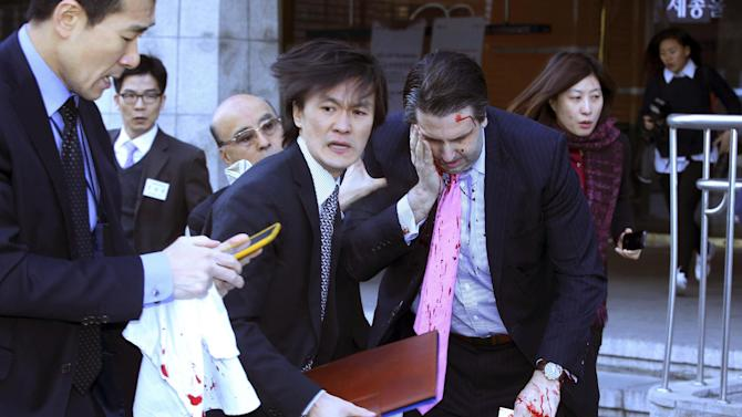 U.S. Ambassador to South Korea Mark Lippert, front right, leaves a lecture hall for a hospital in Seoul, South Korea, Thursday, March 5, 2015, after being attacked by a man. Lippert was attacked by a man wielding a razor and screaming that the rival Koreas should be unified, South Korean police and media said Thursday. (AP Photo/Yonhap, Kim Ju-Sung) KOREA OUT