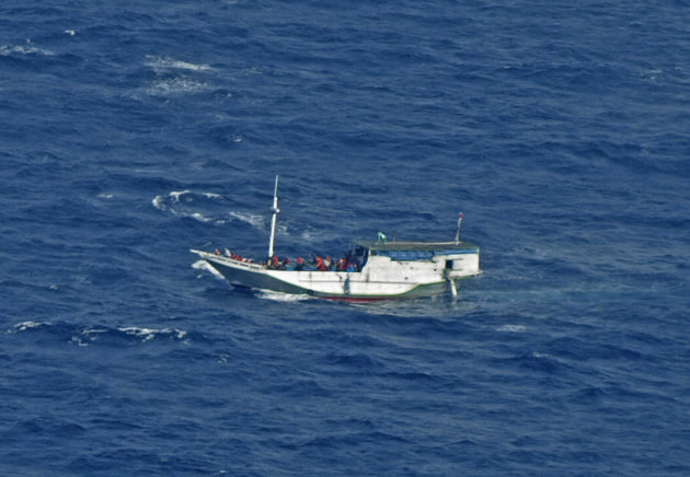 """FILE - In this July 4, 2012 file photo released by the Indonesian National Search And Rescue Agency, a wooden boat which is believed to have up to 180 asylum seekers on board floats on the waters off Christmas Island, Australia. Australia calls it a """"closing-down sale"""" for people smugglers: Asylum-seekers in rickety boats have been reaching its shores in record numbers to avoid a tougher new deportation policy the country is preparing to implement. For many migrants, the price of haste may be death. (AP Photo/Indonesian National Search and Rescue Agency, File)"""