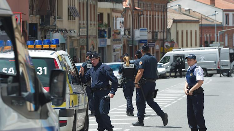 Police officers control the street next to a bank where a man took hostages  in the southern French city of Toulouse, Wednesday, June 20, 2012. A gunman who authorities say had past psychiatric problems took four people hostage Wednesday in a bank in the southern French city of Toulouse, claiming he was acting for religious reasons. (AP Photo/Bruno Martin)