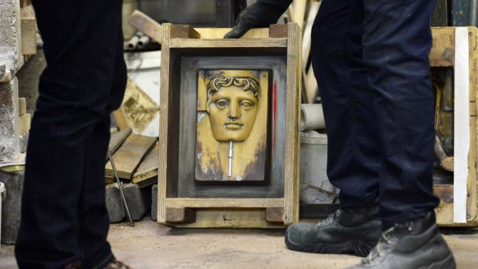 A foundry worker handles  mold frame during the manufacturing process of a BAFTA mask at foundry in west London