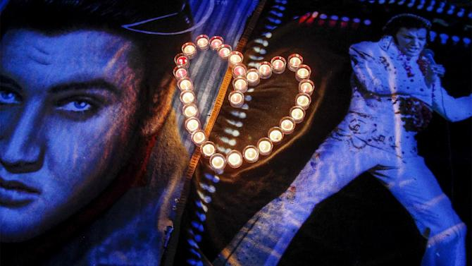 Candles placed in a heart shape rest on Elvis blankets outside the gates of Graceland during a candlelight vigil in remembrance of Elvis' death 37 years-ago, Friday, Aug. 15, 2014, in Memphis, Tenn. (AP Photo/The Commercial Appeal, Mark Weber)