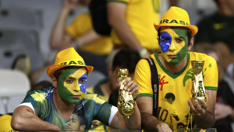 Brazil fans hold trophies upside down after the 2014 World Cup semi-finals between Brazil and Germany at the Mineirao stadium