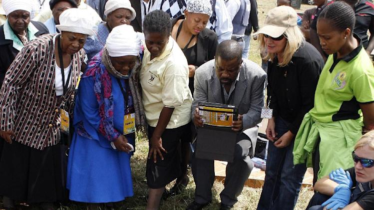 Nomsa Tshabalala, second from left, with relatives surrounding the presumed grave of her son Siboniso Tshabalala, at Avalon Cemetery in Johannesburg, South Africa, on Tuesday, March 12, 2013. Forensic scientists on Tuesday exhumed two bodies believed to belong to young activists last seen 24 years ago at the home of Winnie Madikizela-Mandela, a discovery that has forced a new police murder investigation.   (AP Photo/Themba Hadebe)