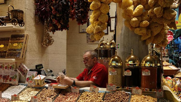 """A man sits in his shop in the 17th century Spice Market, or the Egyptian Bazaar, with stalls beautifully displaying spices, dried fruit, nuts, apple tea, essential oils, and """"Turkish Delight"""" candy in Istanbul, Turkey, Tuesday, Oct. 29, 2013. Last summer, Istanbul's Taksim Square was the scene of violent confrontations between police and protesters. But protests have faded, and contrary to some lingering perceptions, it's quite calm now _ except for the normal hustle and bustle found in this vibrant city. And it's as safe for tourists as it ever was. Istanbul is a thoroughly modern place, but it traces its roots back to 660 B.C. It's the former seat of the opulent Byzantine and Ottoman empires and is divided into European and Asian sides by the Bosporus Strait, offering a wealth of history and stunning scenery.(AP Photo)"""