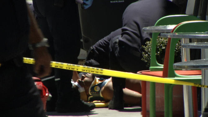 In this frame grab from video, emergency personnel tend to an injured man after a shooting outside a shopping center in San Francisco, Friday July 12, 2013. Two women were killed and a man was wounded on Friday before a suspect covered in blood was arrested at a shopping center in a crowded neighborhood that is home to police headquarters and several tech companies, authorities said. Investigators were trying to determine if the shooting was connected to a botched robbery. (AP Photo/Haven Daley)