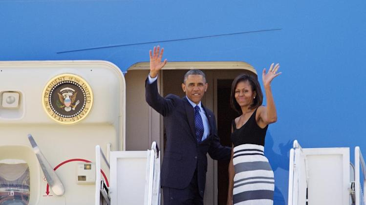 President Barack Obama and first lady Michelle Obama wave prior to boarding Air Force One before departing from Andrews Air Force Base, Md., Wednesday, June 26, 2013, on a week long trip to Senegal, South Africa, and Tanzania. ( AP Photo/Jose Luis Magana)