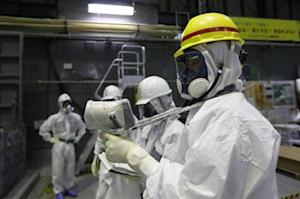 A Tokyo Electric Power Co. (TEPCO) employee wearing a protective suit and mask uses a survey meter near the spent fuel pool inside the No. 4 reactor building at the tsunami-crippled TEPCO's Fukushima Daiichi nuclear power plant in Fukushima prefecture November 7, 2013. REUTERS/Kimimasa Mayama/Pool/Files
