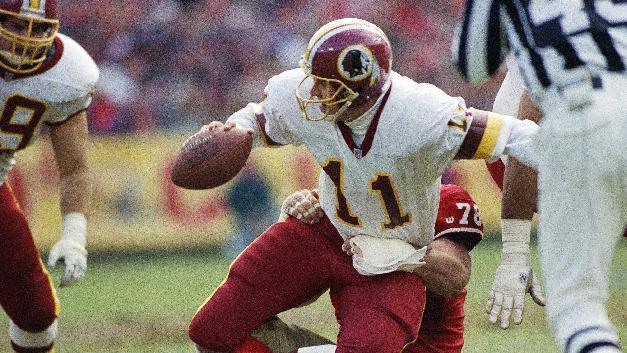 FILE - In this Jan. 9, 1993 file photo, Washington Redskins quarterback Mark Rypien (11) is sacked by San Francisco 49ers' Pierce Holt (78) during an NFL football game in San Francisco. Rypien is a Super Bowl MVP and champion, a former player for the Redskins and other teams who reached football's pinnacle and now wonders at what cost.  (AP Photo/Susan Ragan, File)