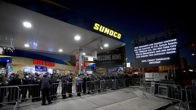 People line up though a gas station after sunset to attend the wake of slain NYPD officer Rafael Ramos at Christ Tabernacle Church in the Queens borough of New York