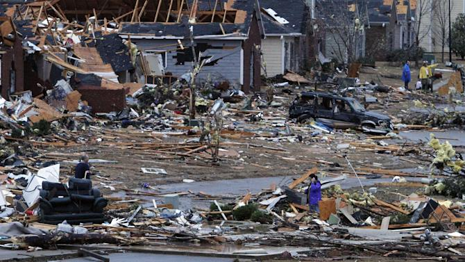 FILE - In this Jan. 23, 2012, file photo, residents walk around through the debris of their neighborhood after a tornado ripped through the Trussville, Ala. area. Storm chasers are watching the Southeast as a nasty storm brews with the potential to spin off a batch of tornadoes. Tornado season is just about here and forecasters believe twisters are possible Thursday and Friday. But in reality, it got an early and deadly start in late January when two people were killed by separate twisters in Alabama. The season usually starts in March and then ramps up for the next couple of months, but forecasting tornado seasons is even more imprecise than predicting hurricane seasons. (AP Photo/Butch Dill)