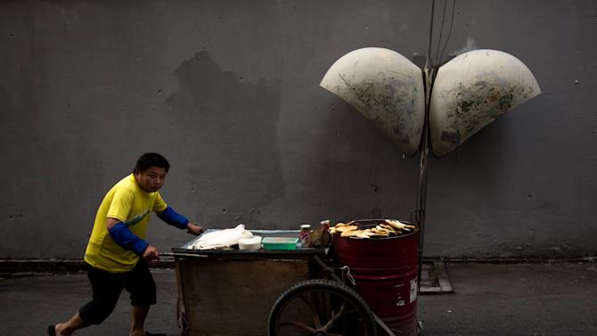 A vendor pushes a cart selling fried buns at a Hutong alley in Beijing, Sunday, Sept. 9, 2012. A jump in food prices pushed China's inflation rate to rise 2 percent in August compared with a year earlier, complicating efforts by the government to revive growth with further stimulus measures. (AP Photo/Andy Wong)