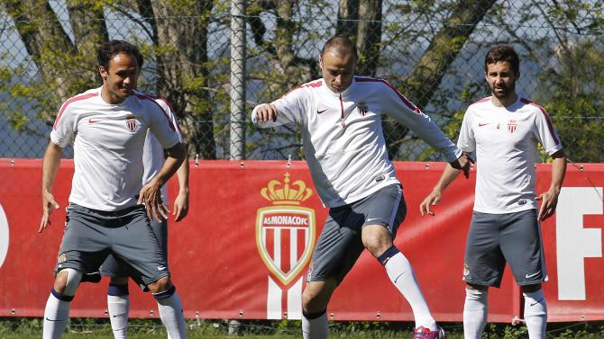 AS Monaco's Dimitar Berbatov kicks the ball surrounded by team-mates Joao Moutinho and  Ricardo Carvalho during a training session on the eve of their Champions League soccer match against Juventus in La Turbie