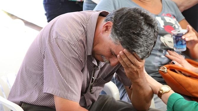 A relative of a victim is comforted in Santa Maria city, Rio Grande do Sul state, Brazil, Sunday, Jan. 27, 2013. A blaze raced through the crowded nightclub in southern Brazil early Sunday, killing more than 200 people as the air filled with deadly smoke and panicked party-goers stampeded toward the exits, police and witnesses said. It appeared to be the world's deadliest nightclub fire in more than a decade.(AP Photo/Evandro Sturm)