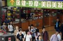 Shoppers walk past small shops at an underground mall in Zhuhai