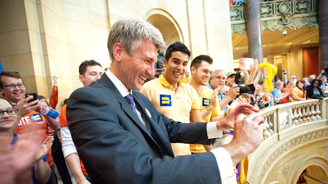 IMAGE DISTRIBUTED FOR HUMAN RIGHTS CAMPAIGN - Minneapolis Mayor R. T. Rybak, left, celebrates with Luis Guitart, center, 21 of Minneapolis and Erik White, right, 26 of Minneapolis after the the Minnesota Senate voted legalize same-sex marriage Monday, May 13, 2013 in St Paul, Minn. Gov. Mark Dayton will sign the bill during a celebratory ceremony at 5 p.m. Tuesday on the steps of the Capitol. (Craig Lassig/AP Images for Human Rights Campaign)