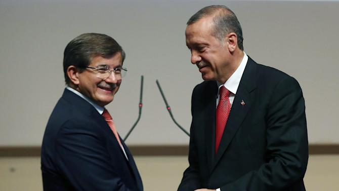 Turkey's president-elect Recep Tayyip Erdogan, right, greets Foreign Minister Ahmet Davutoglu after he announced Davutoglu as his ruling Justice and Development Party's new leader, in Ankara, Turkey, Thursday, Aug. 21, 2014. Davutoglu, hand-picked by president-elect Erdogan to succeed him as prime minister, is expected to accept the largely backseat role although he is known to be an ambitious politician. (AP Photo/Burhan Ozbilici)