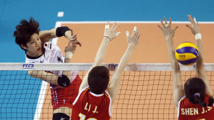 Nagaoka of Japan spikes the ball against Li and Shen of China during their FIVB Women's Volleyball World Grand Prix 2014 final round match in Tokyo