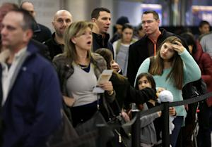Travelers wait in line to board a flight at LaGuardia …