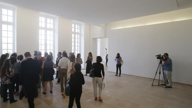 In this Sept. 19, 2014 photo, reporters gather in an empty room during the press day at the Picasso museum in Paris. Paris' Picasso museum is finally allowing the public a glimpse into its shuttered rooms after 5 years of closure over a restoration fraught with setbacks, dismissals and back-stabbings worthy of a Dan Brown thriller. Thought it should be good news for art-lovers since the museum boasts the world's largest Picasso collection one problem remains. It's empty. (AP Photo/Michel Euler)