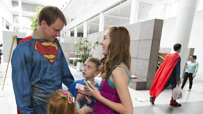 Sears employee, Steve Larson, joins his children after he and colleagues after the Sears and MAN OF STEEL (™) Guinness World Record Superman gathering at the company's corporate headwaters in Hoffman Estates, IL on June 5, 2013.   The employees set a new record as 566 people dressed as Superman for the event.  Sears is celebrating its tie-in to the MAN OF STEEL (™) film, which opens two days before Father's Day. (Ross Dettman/AP Images for Sears)