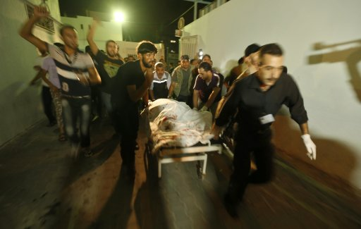 Palestinians wheel the body of a militant at a hospital, following an Israeli air strike in the northern Gaza Strip