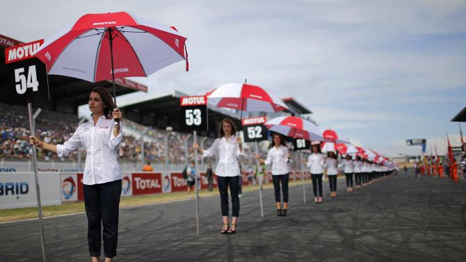 Grid girls are lined up before the Le Mans motorcycling endurance race