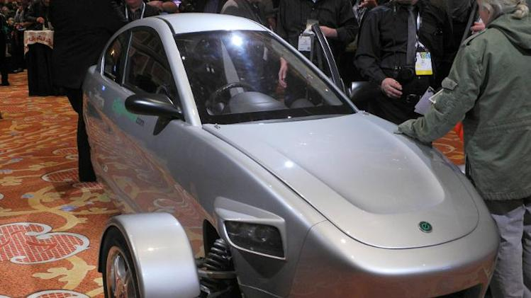 Members of the media inspect a prototype of three-wheeled car, the brainchild of Paul Elio, founder and CEO of Elio Motors, on the sidelines of the 2014 Consumer Electronics Show (CES) January 9, 2014 in Las Vegas