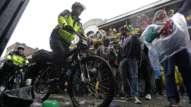 FILE - In this March 4, 2014 file photo, police on bicycles ride through standing water past revelers during Mardi Gras festivities in the French Quarter in New Orleans. A spike in violent crime in the French Quarter is unsettling residents and comes just as New Orleans prepares to host crowds of tourists for Mardi Gras. (AP Photo/Gerald Herbert, File)