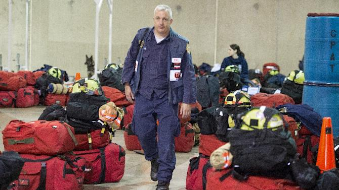 A member of Virginia Task Force 1, Fairfax Urban Search and Rescue Team walks among the packed bags of search and rescue members at their Chantilly, Virginia headquarters, before deploying to Nepal on April  25, 2015