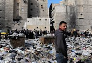 Syrian people are pictured in a bazaar next to a garbage heap in the northern city of Aleppo, on February 14, 2013. Syria&#39;s rebels captured a military airbase in the northern province of Aleppo and geared for a major battle against loyalist forces for control of two nearby strategic airports
