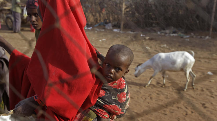 A child with its mother after they were handed food at a World Food Programme, WFP,  compound in a displacement camp in Dadaab, Kenya, Sunday, July 31, 2011. Dadaab, a camp designed for 90,000 people now houses around 440,000 refugees. Almost all are from war-ravaged Somalia. Some have been here for more than 20 years, when the country first collapsed into anarchy. But now more than 1,000 are arriving daily, fleeing fighting or hunger.(AP Photo/Schalk van Zuydam)