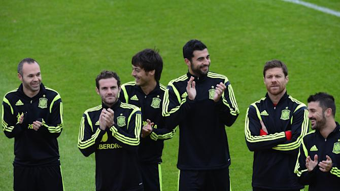 Spain's players, Andres Iniesta, from left to right, Juan Mata, David Silva, Raul Albiol, Xabi Alonso, and David Villa, applaud during a promotional event, before the start of a training session at the Atletico Paranaense training center in Curitiba, Brazil, Tuesday, June 10, 2014. Spain will play in group B of the Brazil 2014 World Cup
