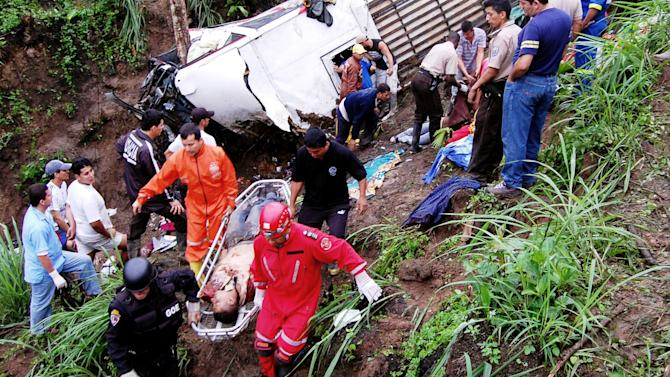 Policemen and firefighters carry the body of a passenger after a bus plunged into a ravine in San Isidro, southwest of Quito, Ecuador, Friday, Dec. 24, 2010. At least 35 people were killed and 32 were reported injured in the accident. (AP Photo/Str)
