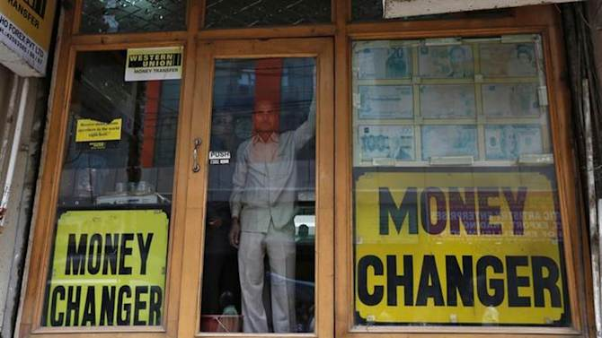 Two men look out from the glass door of a currency exchange shop in New Delhi August 30, 2013. REUTERS/Mansi Thapliyal