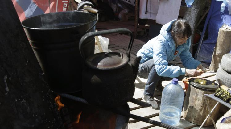 A pro-Russian supporter prepares food in their camp near the seized office of the SBU state security service in Luhansk