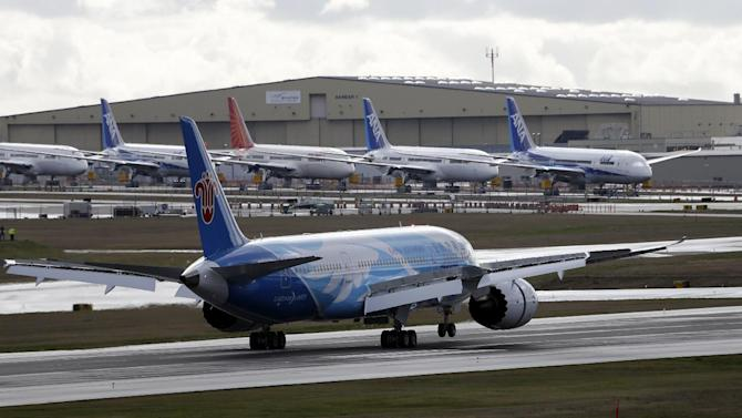 This photo taken Feb. 7, 2013 show a Boeing 787 jet landing, in view of a line of parked 787's at Paine Field in Everett, Wash. Boeing has developed a plan that it intends to propose to federal regulators to temporarily fix problems with the 787 Dreamliner's batteries that have kept the planes on the ground for more than a month, a congressional official told The Associated Press.  (AP Photo/Elaine Thompson)